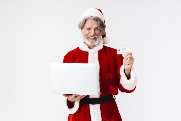 Portret szczęśliwego siwego mężczyzny świętego mikołaja w czerwonym stroju, trzymającego laptopa i kartę kredytową na białym tle