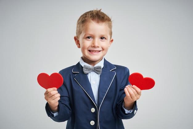 Portret szczęśliwego słodkiego małego dziecka trzymającego czerwone serce i patrzącego na kamerę na białym tle nad szarym tłem