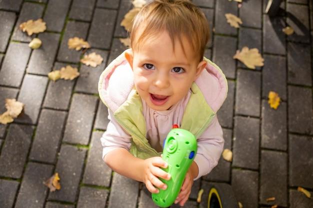 Portret szczęśliwego słodkiego malucha grającego w telefon z zabawkami w jesiennym parku