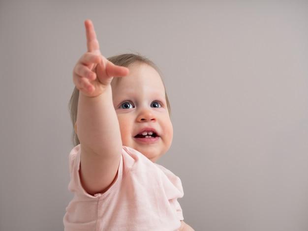 Portret szczęśliwego śmiejącego się dziecka, ze śmiesznym wyrazem twarzy. mała piękna dziewczyna o niebieskich oczach uśmiecha się radośnie i wskazuje palcem w górę, pokazując pierwsze zęby.