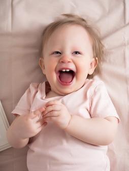 Portret szczęśliwego śmiejącego się dziecka, ze śmiesznym wyrazem twarzy. mała piękna dziewczyna o niebieskich oczach uśmiecha się radośnie, widoczne są pierwsze zęby.