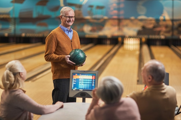 Portret szczęśliwego starszego mężczyzny uśmiechającego się do grupy przyjaciół podczas wspólnej gry w kręgle w centrum rozrywki, kopia przestrzeń