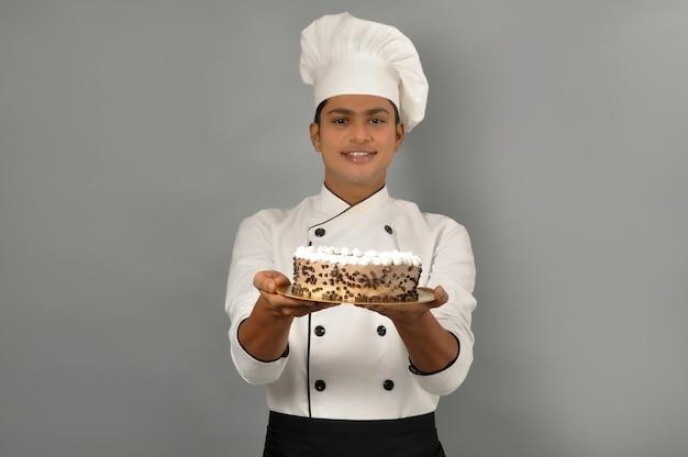 Portret szczęśliwego szefa kuchni męskiej ubranego w mundur trzymający talerz z ciastem czekoladowym