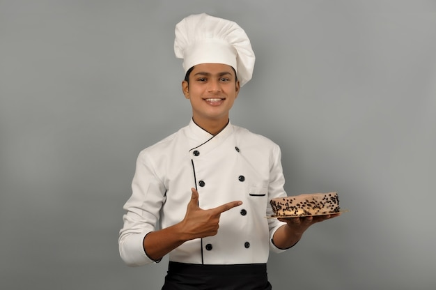 Portret szczęśliwego szefa kuchni mężczyzny ubranego w mundur trzymający talerz z ciastem czekoladowym wskazując na tort