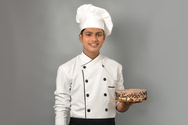 Portret szczęśliwego szefa kuchni mężczyzny ubranego w mundur trzymający talerz z czekoladowym ciastem, patrząc na kamerę