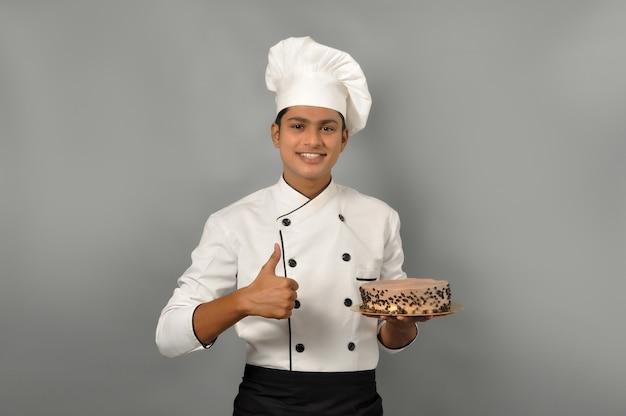 Portret szczęśliwego szefa kuchni mężczyzny ubranego w mundur trzymający talerz z czekoladowym ciastem z kciukiem do góry