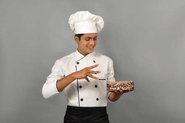 Portret szczęśliwego szefa kuchni mężczyzny ubranego w mundur trzymający talerz z czekoladowym ciastem z pozą magika