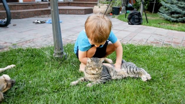 Portret szczęśliwego uśmiechniętego 3-letniego chłopca pieszczącego i bawiącego się z kotem leżącym na trawie w ogrodzie przydomowym domu house