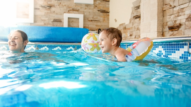 Portret szczęśliwego uśmiechniętego chłopca bawiącego się nadmuchiwaną kolorową piłką plażową z matką w krytym basenie