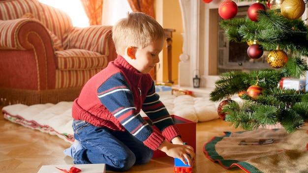 Portret szczęśliwego uśmiechniętego chłopca biorącego zabawki z świątecznego pudełka i bawiącego się na podłodze pod choinką