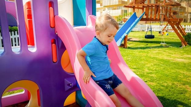 Portret szczęśliwego uśmiechniętego chłopca jadącego na kolorowej plastikowej zjeżdżalni na placu zabaw dla dzieci w parku