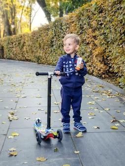 Portret szczęśliwego uśmiechniętego chłopca z hulajnogą trzyma sok w parku