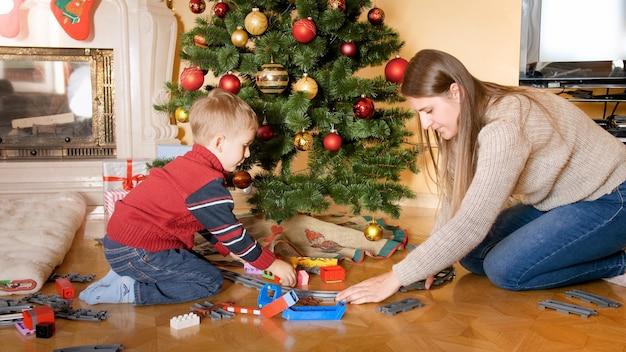 Portret szczęśliwego uśmiechniętego chłopca z matką buduje kolej i bawi się zabawkowym pociągiem na podłodze pod piękną choinką