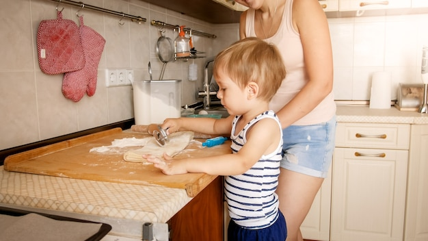Portret szczęśliwego uśmiechniętego chłopca z młodą matką do pieczenia i gotowania w kuchni