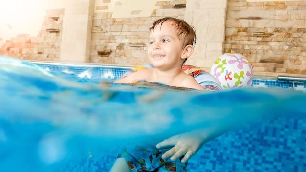 Portret szczęśliwego wesołego chłopca bawiącego się nadmuchiwaną piłką plażową i kolorowym pierścieniem na krytym basenie w domu