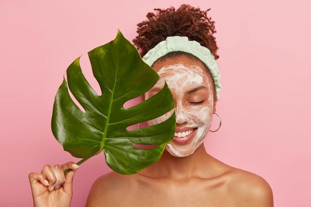 Portret szczęśliwej afroamerykanki zakrywa połowę twarzy zielonym liściem, czyści twarz, myje się mydłem bąbelkowym, stoi topless, dba o urodę i ciało