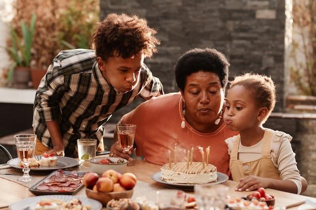 Portret szczęśliwej afrykańskiej babci świętującej urodziny z rodziną i dmuchającej świece...