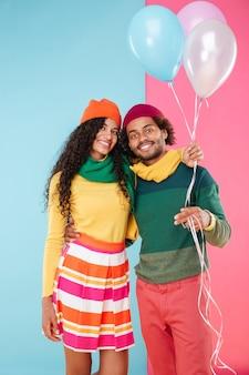Portret szczęśliwej afrykańskiej młodej pary w czapkach i szalikach z balonami