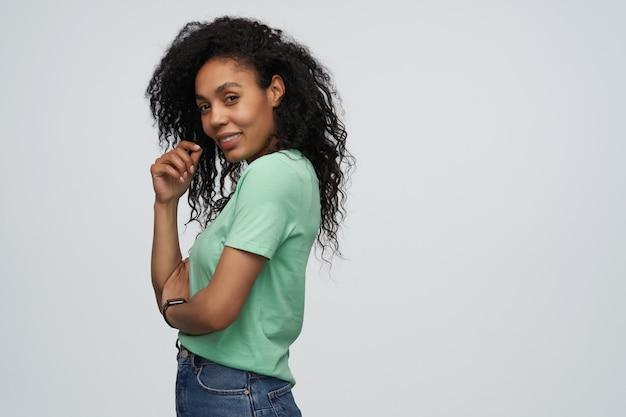 Portret szczęśliwej atrakcyjnej młodej kobiety z długimi kręconymi włosami w miętowej koszulce, uśmiechniętej i patrzącej na przód izolowanej nad szarą ścianą