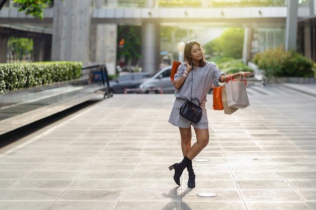 Portret szczęśliwej azjatki idącej i trzymającej torbę na zakupy w centrum miasta
