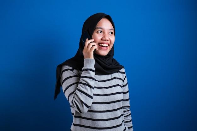 Portret szczęśliwej azjatyckiej kobiety noszącej hidżab dzwoniącej z telefonu komórkowego na niebieskim tle