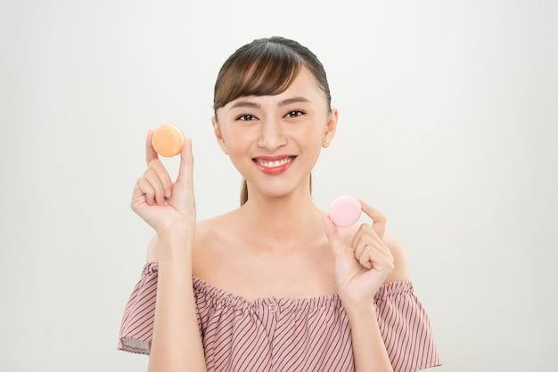 Portret szczęśliwej azjatyckiej kobiety trzymającej makaroniki