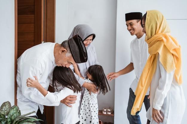 Portret szczęśliwej azjatyckiej rodziny muzułmańskiej odwiedzającej dziadków na ramadan kareem. indonezyjczycy świętują eid mubarak
