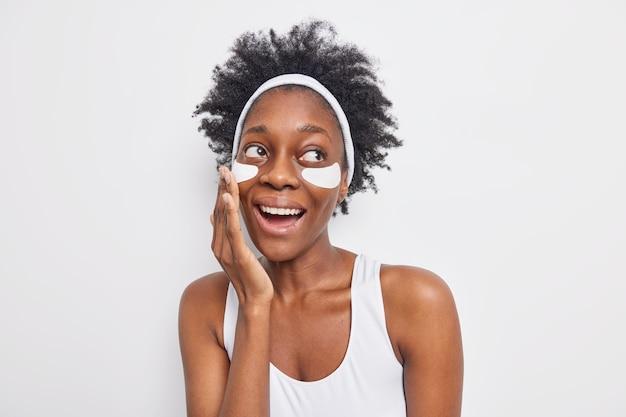 Portret szczęśliwej, beztroskiej kobiety o ciemnej karnacji z naturalnymi kręconymi włosami nakłada łaty upiększające szeroko zmniejsza drobne zmarszczki uśmiechu