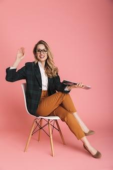 Portret szczęśliwej bizneswoman 30s w stylowym stroju, trzymającej papierowe dokumenty z raportem, siedząc na krześle odizolowanym na czerwono
