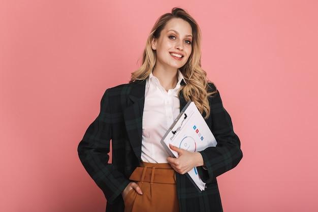 Portret szczęśliwej bizneswoman noszącej kurtkę trzymającą schowek z wykresem na różowym tle