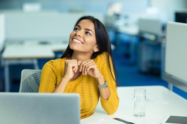 Portret szczęśliwej bizneswoman siedzącej w swoim miejscu pracy w biurze i patrzącej w górę