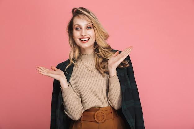 Portret szczęśliwej blond kobiety 30 lat w stylowym stroju uśmiecha się i pozuje na czerwono