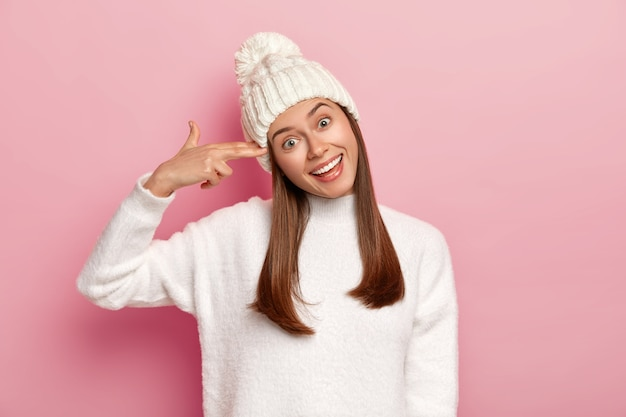 Portret szczęśliwej brunetki strzela w świątyni, przechyla głowę i uśmiecha się szeroko, pokazuje pistolet na palec, nosi zimową czapkę i sweter, odizolowane na różowym tle.