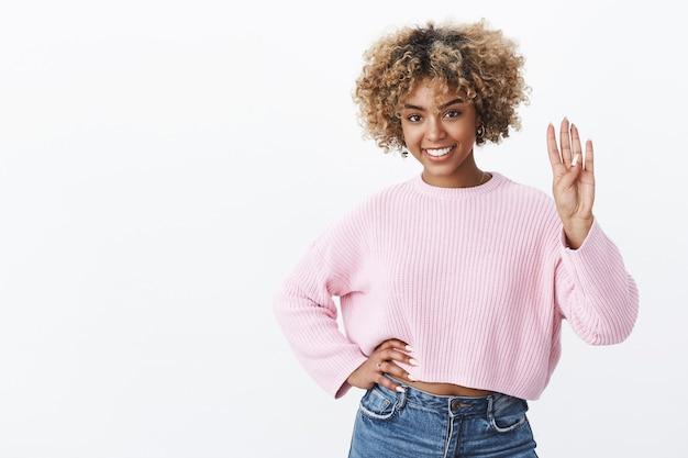 Portret szczęśliwej charyzmatycznej ciemnoskórej kobiety z blond fryzurą afro uśmiechającą się zachwyconą i pewną siebie trzymającą rękę w talii pokazującą numer cztery z podniesioną ręką jako składającą zamówienie