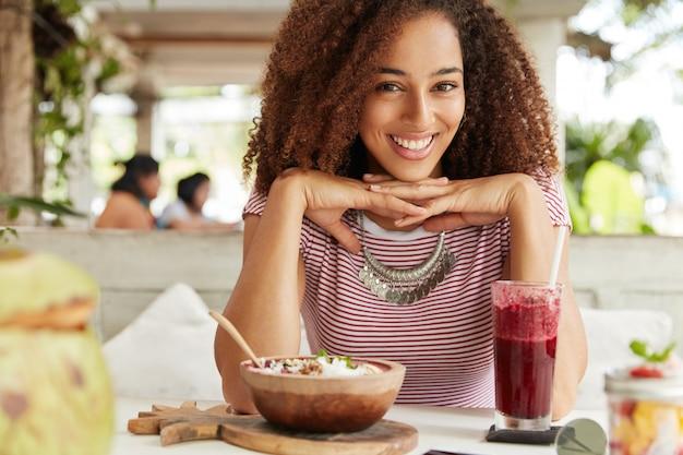 Portret szczęśliwej ciemnoskórej młodej kobiety z kędzierzawymi włosami, je coś i pije smoothie, spędza wolny czas z chłopakiem lub przyjacielem, spędza wakacje w tropikalnym kraju na wyspie