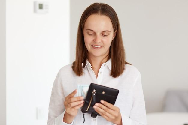 Portret szczęśliwej ciemnowłosej kobiety w białej koszuli w stylu casual, trzymającej portfel z banknotami w dłoni, liczącej pieniądze, mającej pozytywny wyraz twarzy.