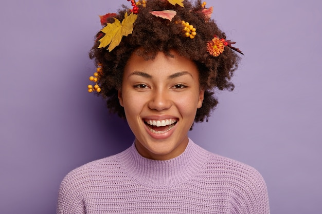Portret szczęśliwej delikatnej kobiety z fryzurą afro uśmiecha się szeroko, pokazuje białe zęby, cieszy się dobrą zabawą, ma jesienne liście w głowie