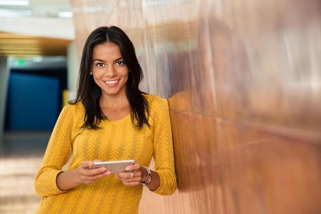 Portret szczęśliwej dorywczo bizneswoman używającej smartfona w korytarzu