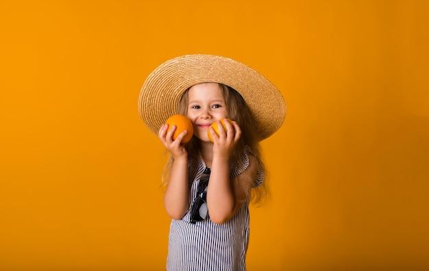 Portret szczęśliwej dziewczynki w słomkowym kapeluszu, trzymając cytrynę i pomarańczy na żółtej powierzchni z miejscem na tekst