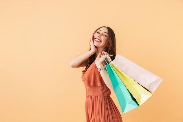 Portret szczęśliwej dziewczyny 20s niosących kolorowe papierowe torby na zakupy, stojąc odizolowane