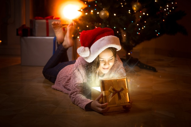 Portret szczęśliwej dziewczyny leżącej na podłodze i patrzącej do wnętrza magicznego pudełka