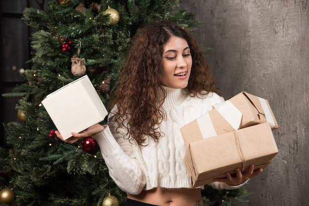Portret szczęśliwej dziewczyny patrzącej na prezenty w opakowaniu