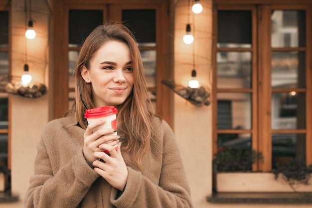 Portret szczęśliwej dziewczyny stoi na tle brązowej ściany z filiżanką kawy w dłoniach, nosi wiosenne ubrania, patrzy w bok i uśmiecha się
