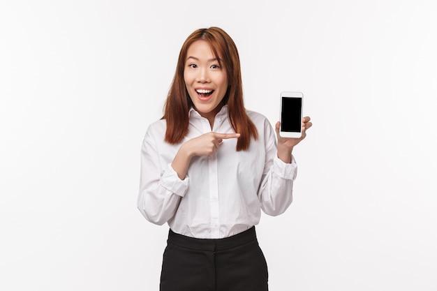 Portret szczęśliwej eleganckiej młodej ładnej azjatyckiej kobiety w białej koszuli, wprowadzenie nowej aplikacji lub reklamowanie strony internetowej firmy, programu, palcem wskazującym na telefon komórkowy,