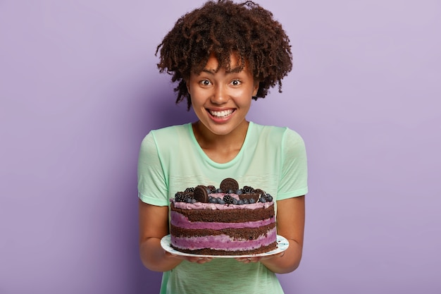 Portret szczęśliwej gospodyni o ciemnej karnacji demonstruje pyszne ciasto upieczone przez siebie, chce traktować gości, ma dobre zdolności coolinary