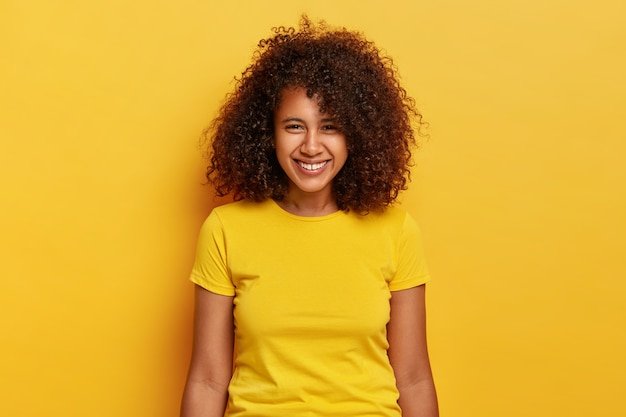 Portret szczęśliwej hipsterki śmieje się pozytywnie, chichocze i uśmiecha się beztrosko, nosi jasnożółte ubranie, ma niewielką szczelinę między zębami, czuje się zachwycona, pozuje w domu, ma naturalne piękno