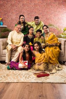 Portret szczęśliwej indyjskiej rodziny w tradycyjnym stroju siedzącej na kanapie w pomieszczeniu