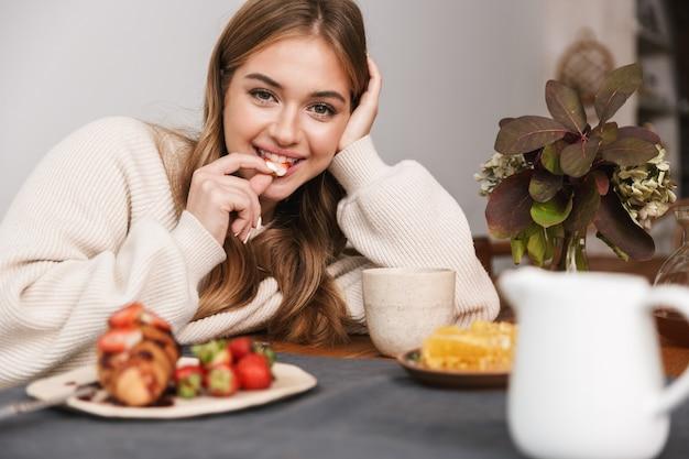Portret szczęśliwej kaukaskiej kobiety noszącej zwykłe ubrania jedzącej truskawki podczas śniadania w przytulnym pokoju