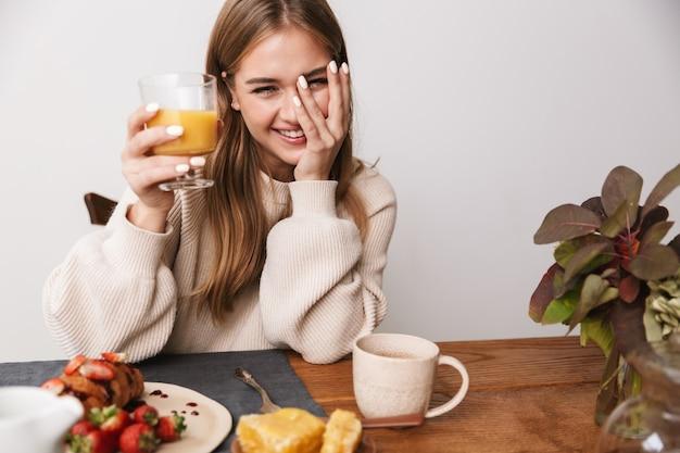 Portret szczęśliwej kaukaskiej kobiety noszącej zwykłe ubrania, śmiejącej się podczas śniadania w przytulnym pokoju