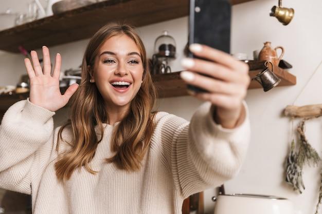 Portret szczęśliwej kaukaskiej kobiety ubranej w zwykłe ubrania, która robi selfie na smartfonie i macha ręką w przytulnej kuchni